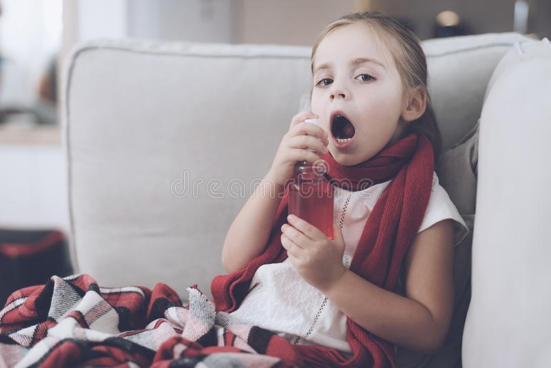 La piccola ragazza malata si siede su uno strato bianco avvolto in una sciarpa rossa Spruzza la sua gola con uno spruzzo medicina immagine stock libera da diritti