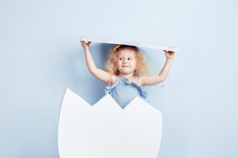 La piccola ragazza riccia incantante nel vestito blu-chiaro è sembrato covare dal grande uovo bianco sui precedenti di immagine stock libera da diritti