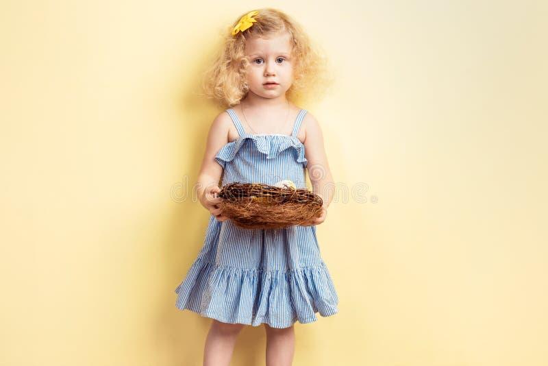 La piccola ragazza riccia incantante nel vestito blu-chiaro tiene il nido con le uova sui precedenti della parete gialla fotografia stock
