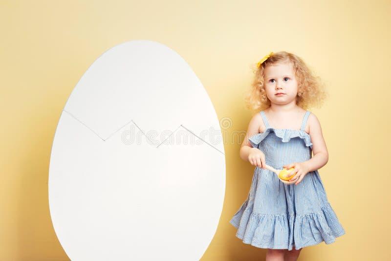 La piccola ragazza riccia incantante nel vestito blu-chiaro tiene un cucchiaio di legno con una condizione tinta dell'uovo accant fotografia stock