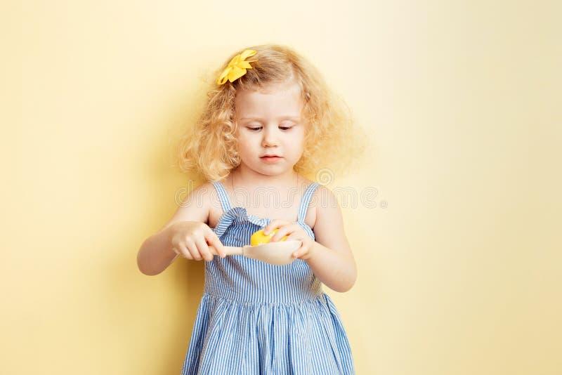 La piccola ragazza riccia incantante nel vestito blu-chiaro tiene un cucchiaio di legno con un uovo tinto sui precedenti di giall fotografia stock libera da diritti