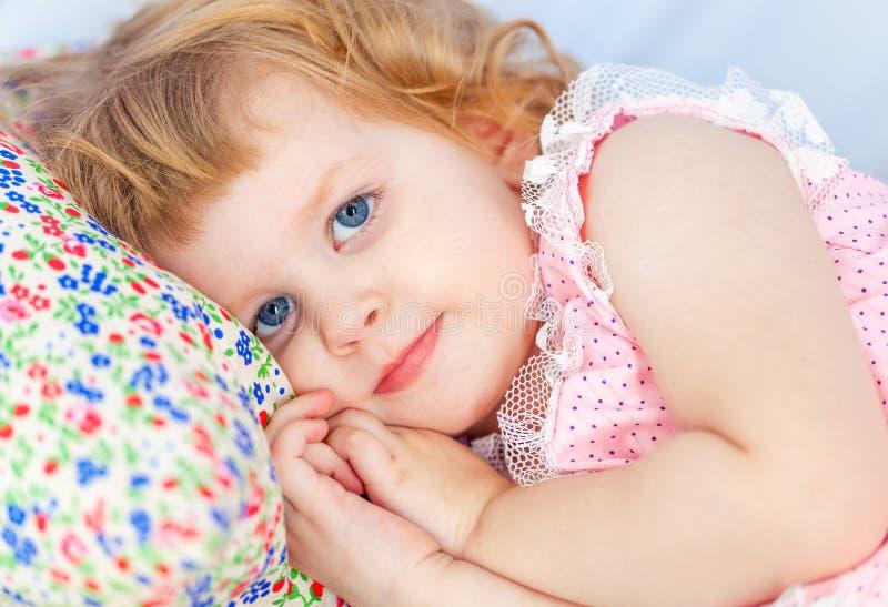 La piccola ragazza riccia sveglia si trova in un letto di bambino ed in una mano sotto la sua guancia immagine stock