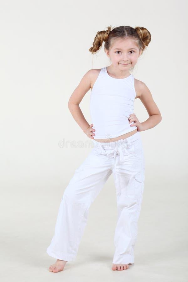 La piccola ragazza sorridente in vestiti bianchi sta e posa. immagine stock libera da diritti