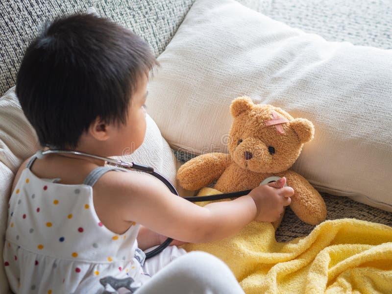 La piccola ragazza sveglia felice sta giocando al dottore con lo stetoscopio ed è immagine stock