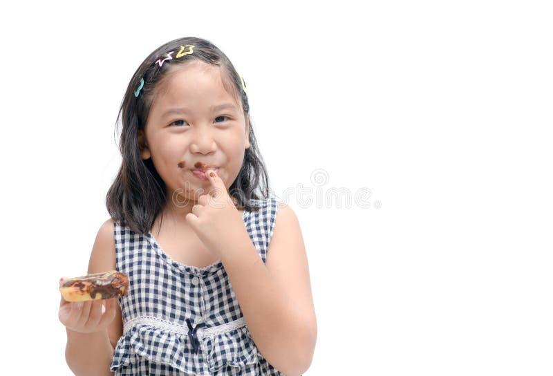 La piccola ragazza sveglia felice sta mangiando la ciambella isolata fotografie stock libere da diritti