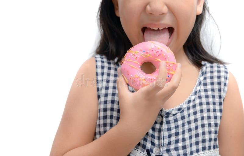 La piccola ragazza sveglia felice sta mangiando la ciambella isolata fotografia stock