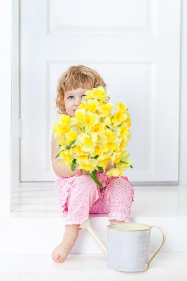 La piccola ragazza sveglia in vestito rosa che si siede sul portico rustico bianco e nasconde il suo fronte dietro il mazzo dei f fotografia stock