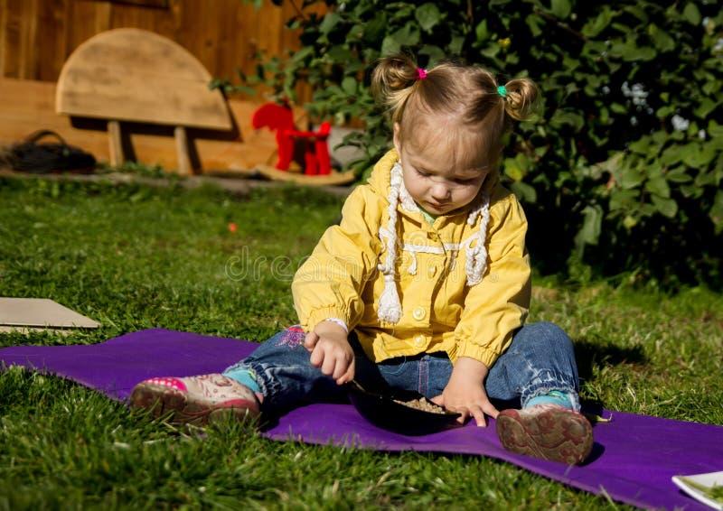 La piccola ragazza triste si siede su un'erba ed esamina l'alimento immagini stock