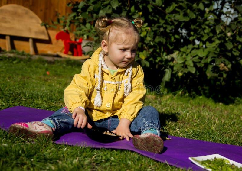 La piccola ragazza triste si siede su un'erba ed esamina l'alimento immagine stock