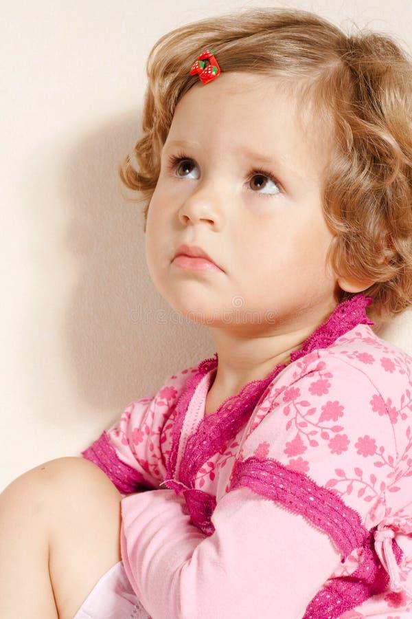 La piccola ragazza triste sta osservando in su fotografia stock