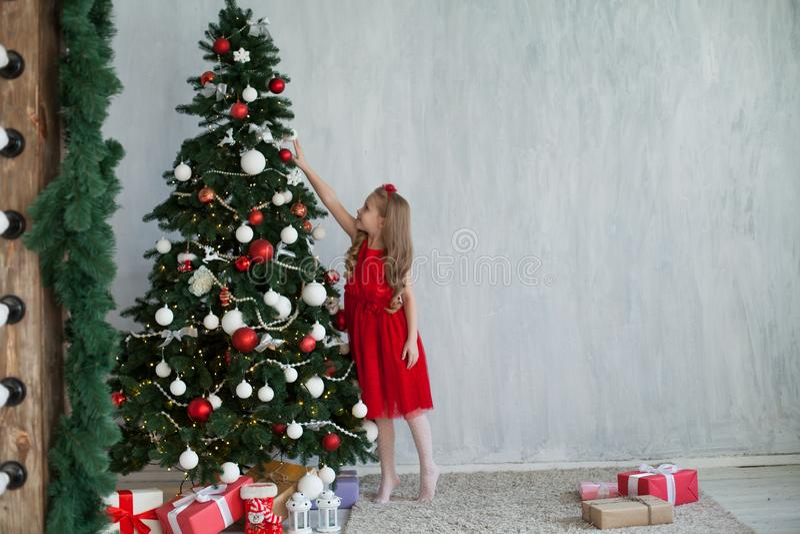 La piccola ragazza in un vestito rosso è decorata con la festa del nuovo anno dei regali di Natale fotografie stock libere da diritti