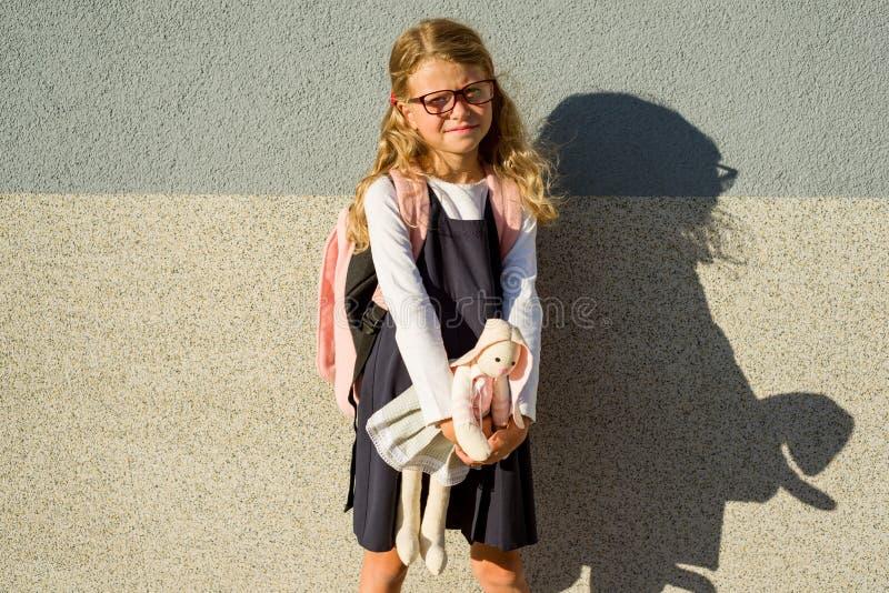 La piccola scolara ha preso il suo giocattolo alla scuola con lei fotografia stock