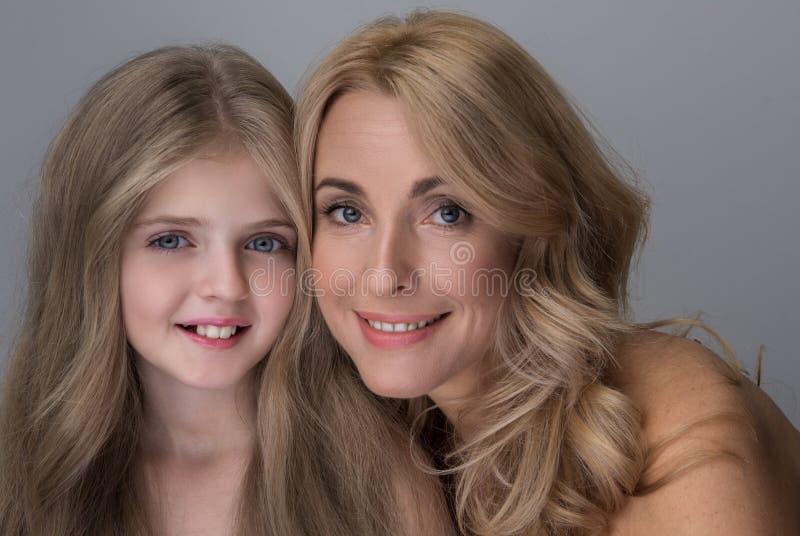 La piccole ragazza e donna felici sono sorridenti ed esprimenti la letizia fotografia stock libera da diritti