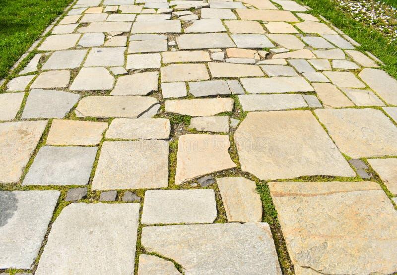 La piedra bloquea el pavimento en el parque de la ciudad Camino hecho con las piedras asimétricas grandes foto de archivo
