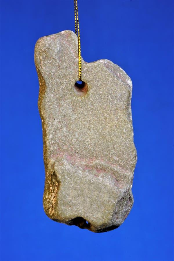 La piedra con un agujero de dios natural del pollo del origen-, durante épocas paganas, fue utilizada como un amuleto y talismán, fotos de archivo libres de regalías