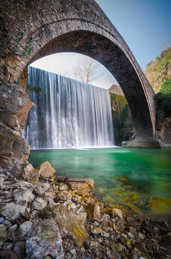 La piedra vieja de Paleokarya arqueó el puente entre dos cascadas Prefectura de Trikala, Grecia imagen de archivo libre de regalías