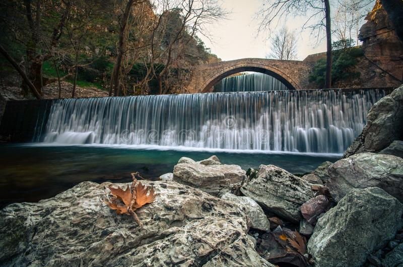 La piedra vieja de Paleokarya arqueó el puente entre dos cascadas Prefectura de Trikala, Grecia fotos de archivo libres de regalías