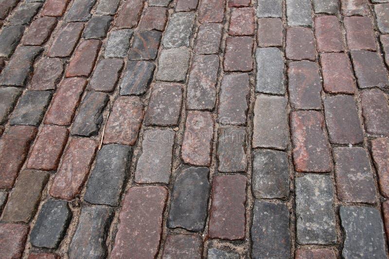 La piedra vieja pavimentó el camino de la calle de la avenida, ángulo bajo foto de archivo libre de regalías