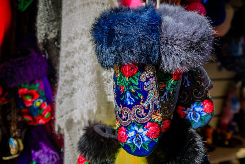 La piel arregló guantes con diseño ruso tradicional repite en venta en un mercado del aire abierto en St Petersburg, Rusia con imagen de archivo