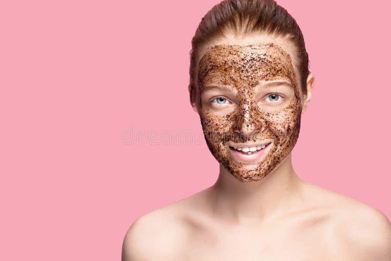 La piel de la cara friega El retrato de la máscara modelo femenina sonriente atractiva de Applying Natural Coffee, cara friega en foto de archivo