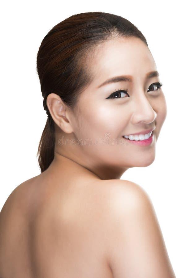 La piel perfecta conmovedora de la mujer asiática hermosa de la belleza, mira detrás imágenes de archivo libres de regalías