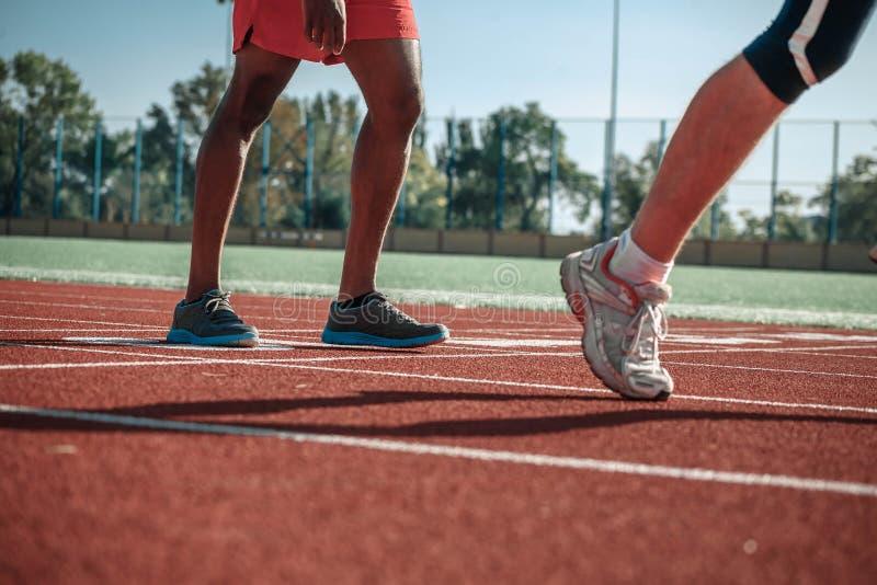 La pierna blanca del ` s del atleta rasga adelante, dejando al hombre negro detrás fotos de archivo libres de regalías