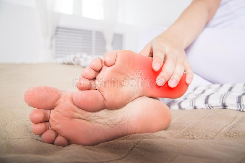 La pierna del ` s de la mujer daña, el dolor en el talón, masaje de pies femeninos foto de archivo