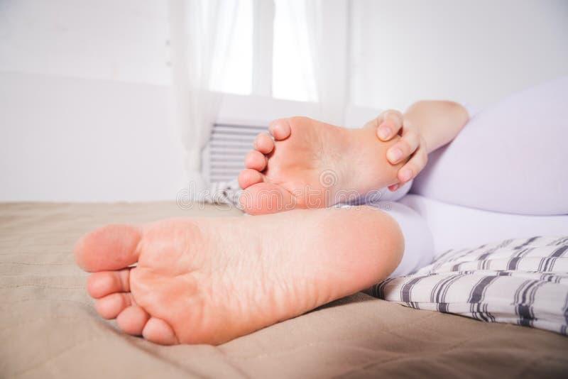 La pierna del ` s de la mujer daña, el dolor en el talón, masaje de pies femeninos foto de archivo libre de regalías