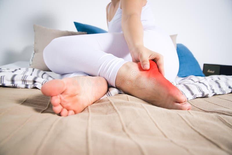 La pierna del ` s de la mujer da?a, el dolor en el tal?n, masaje de pies femeninos imagen de archivo libre de regalías