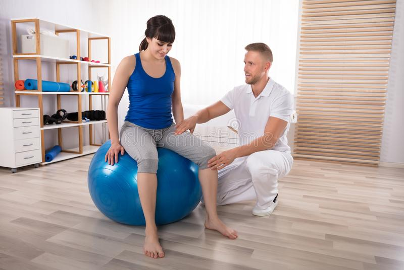 La pierna herida de Examining Smiling Woman masculino del fisioterapeuta fotos de archivo