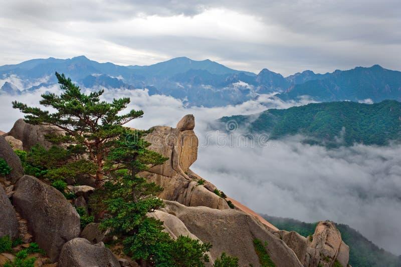 La pierre accrochante à la roche d'Ulsanbawi contre le seorak de brouillard montent images libres de droits