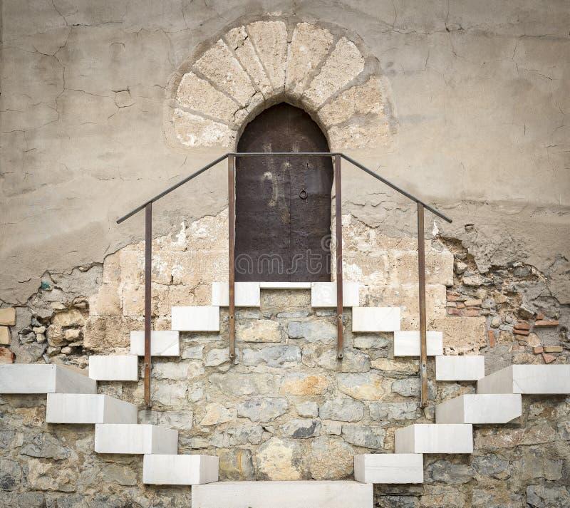 La pierre antique a fait le mur avec une porte métallique rouillée et un escalier photos stock