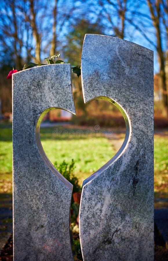 La pierre grave avec le coeur et défraîchie s'est levée image stock