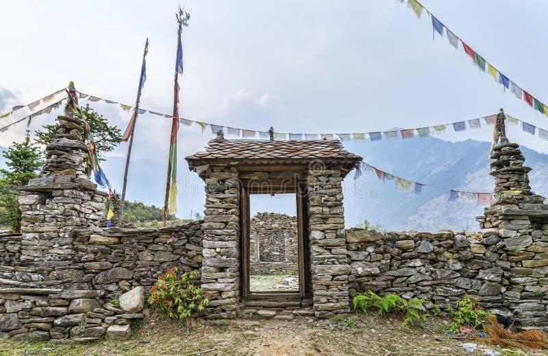 La pietra buddista ha fatto il portone con le bandiere di preghiera immagini stock
