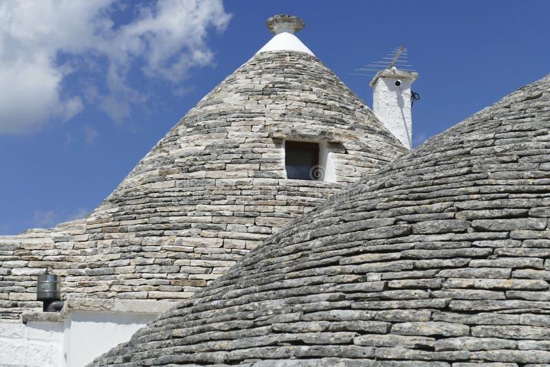 La pietra coned i rooves delle case di trulli immagine stock