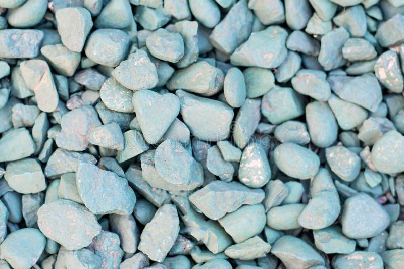 La pietra in forma di cuore blu si trova contro lo sfondo di altre pietre blu fotografie stock libere da diritti