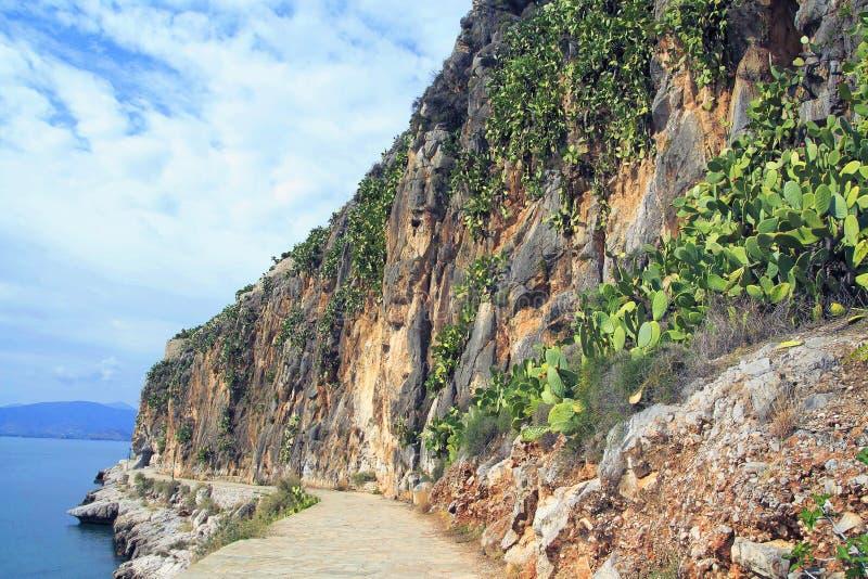 La pietra ha pavimentato il vicolo lungo il mare in Nafplio, Grecia fotografie stock libere da diritti