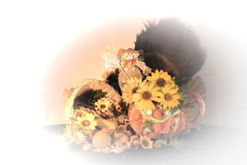 La pieza central de la cornucopia de la acción de gracias con las plumas del pavo de los girasoles y el espantapájaros que celebr imagen de archivo libre de regalías