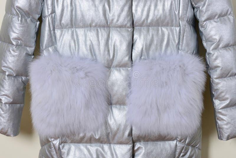 La pieza de la chaqueta plateada con el cuello de la piel y la piel embolsa, primer fotos de archivo libres de regalías