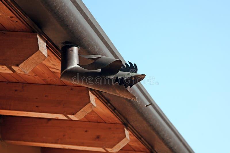 La pieza del tejado con forma de los pescados del canal del metal Casa de madera debajo del cielo azul Detalle constructivo del a imagen de archivo libre de regalías