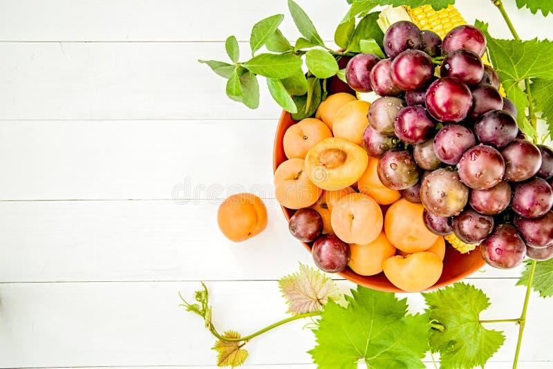 La pila de albaricoques, las uvas y los granos en una placa anaranjada con las hojas verdes frescas en el plano de madera blanco  fotos de archivo libres de regalías