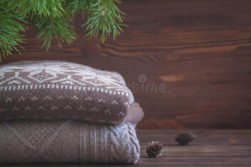 La pila de beige hizo punto la ropa en fondo de madera, suéteres, géneros de punto del invierno imágenes de archivo libres de regalías