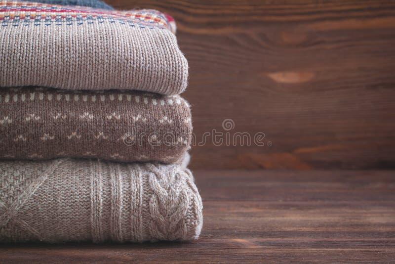 La pila de beige hizo punto la ropa en fondo de madera, suéteres, géneros de punto del invierno fotografía de archivo libre de regalías
