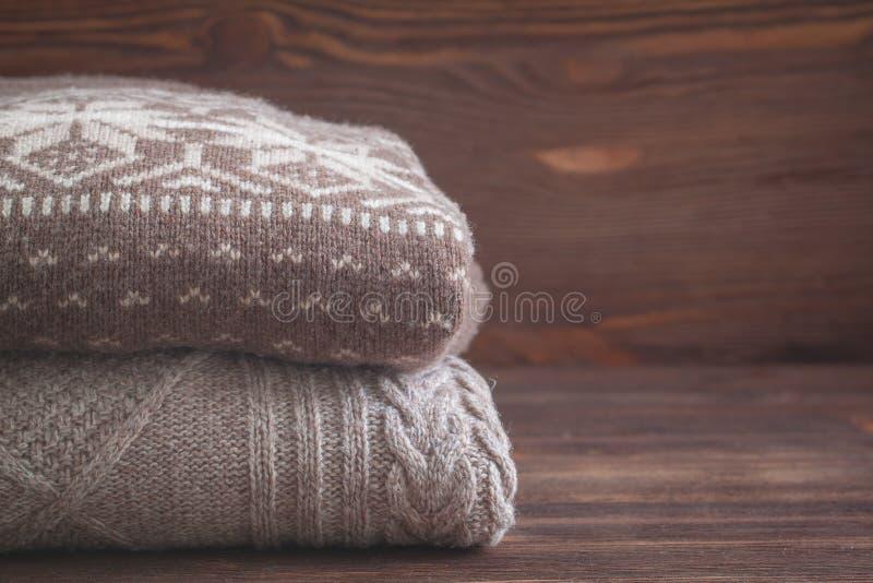 La pila de beige hizo punto la ropa en fondo de madera, suéteres, géneros de punto del invierno fotos de archivo libres de regalías