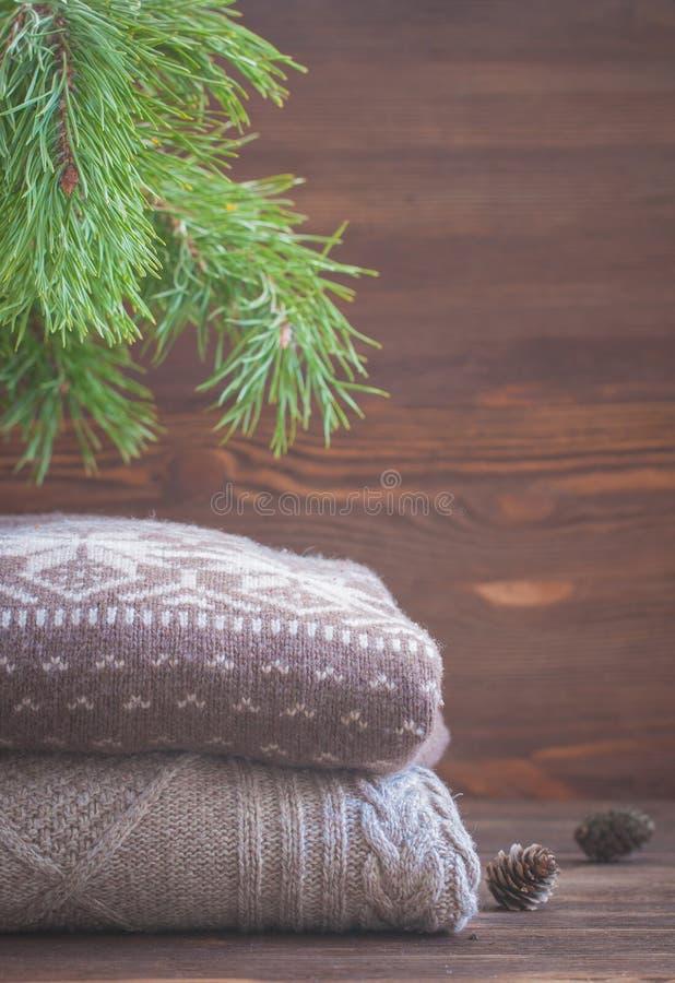 La pila de beige hizo punto la ropa en fondo de madera, suéteres, géneros de punto del invierno imagen de archivo libre de regalías