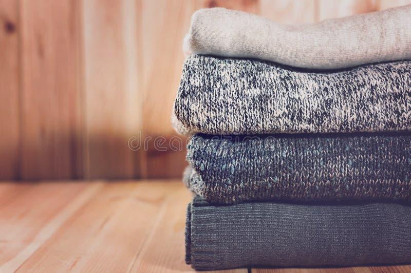 La pila de gris hizo punto la ropa en fondo de madera, suéteres, géneros de punto del invierno, en un ajuste rústico fotos de archivo libres de regalías