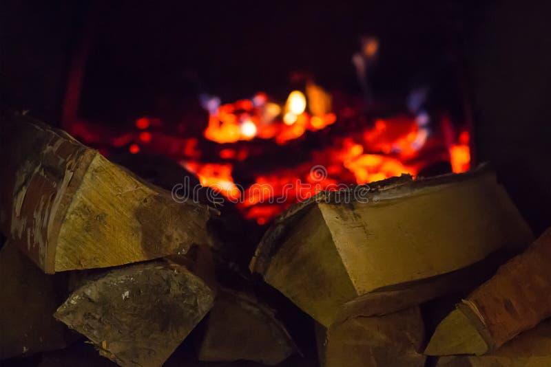 La pila de leña saltada encendió la luz caliente de la lámpara, combustible para el fuego de la chimenea secado en un fondo borro fotos de archivo libres de regalías