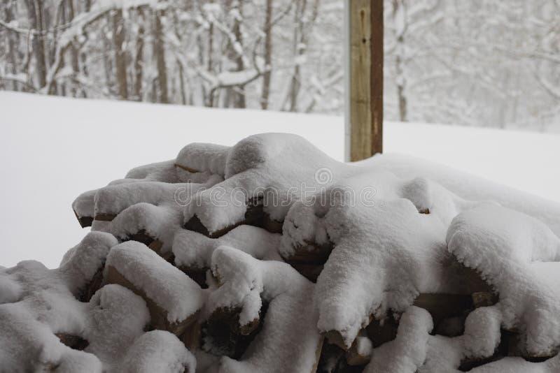 La pila de madera se cubre con nieve fotografía de archivo libre de regalías