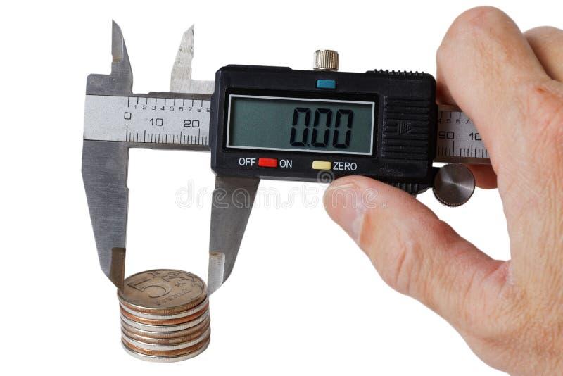 La pila de monedas medidas con un calibrador adentro sirve la mano imagen de archivo