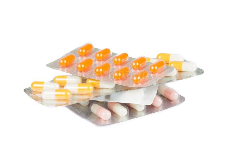 La pila de píldoras y de cápsulas de la medicina embaló en las ampollas aisladas foto de archivo libre de regalías